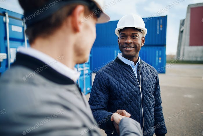 Smiling engineers standing in a freight yard shaking hands together