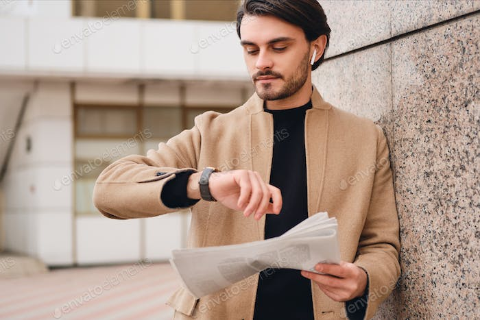 Young handsome stylish man in beige coat with newspaper dreamily watching time on watch outdoor