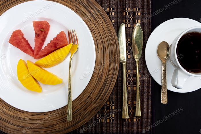 Golden cutlery laid on a table with a plate, melon and a cup