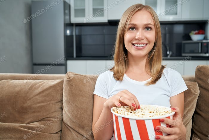 Young woman watching movie and eating popcorn at home