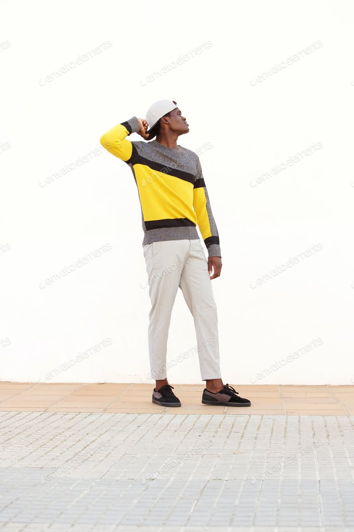 Full length stylish young african man standing outside and looking away