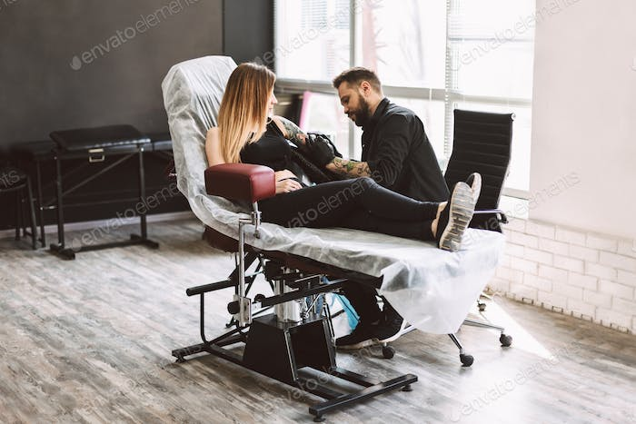 Professional tattooer carefully doing tattoo on girl hand using