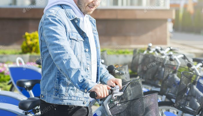 Millennial guy taking bicycle for riding to work at public station
