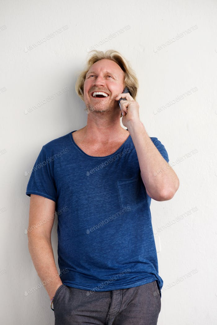happy man standing by a wall and talking on mobile phone