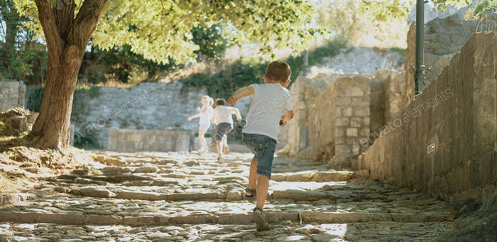 Children run through the summer park, the view from the back.