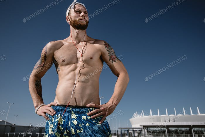 Relaxing after training on workout ground outdoors. Handsome shirtless sportsman looking away with