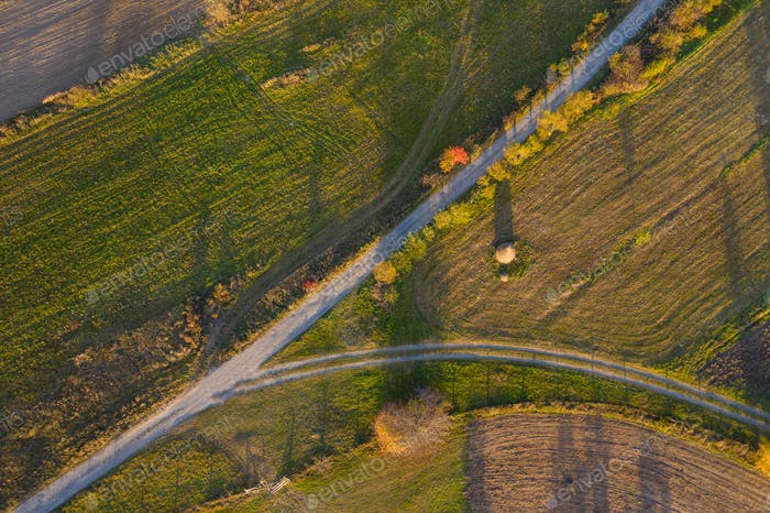 Aerial drone view of a countryside dirt road at autumn