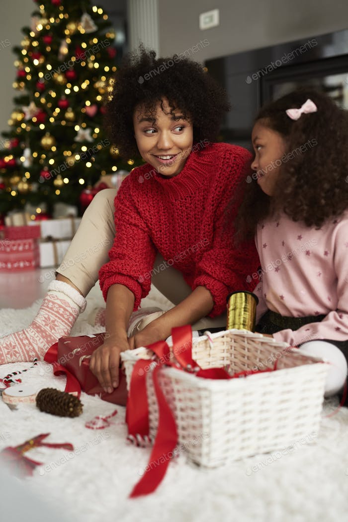 Close up of girls packing gifts for Christmas