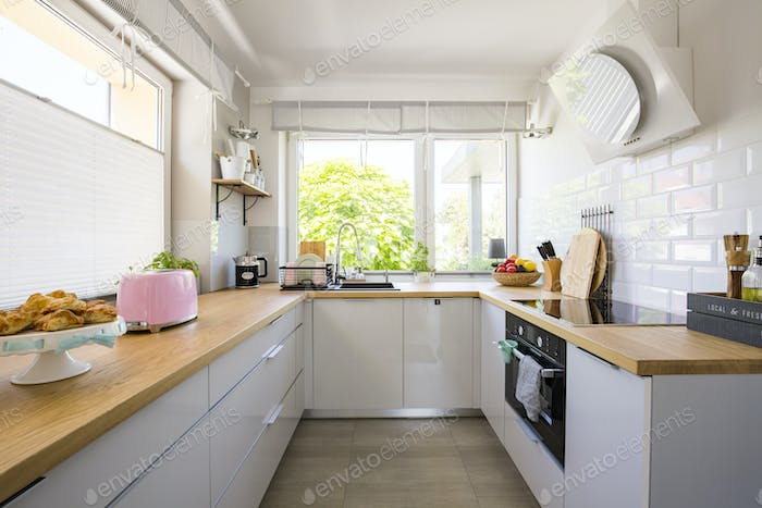 Windows in white kitchen interior with grey cabinets and wooden