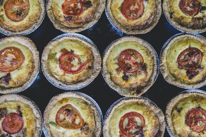 Hochwinkel Nahaufnahme von frisch gebackenen Quiches mit einem Käse- und Tomaten-Topping.