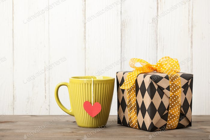 Wrapped gift box and cup on wooden table