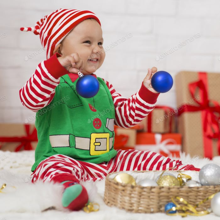 Happy baby elf enjoying Christmas home decoration