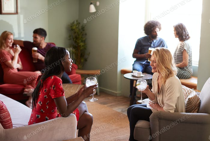 Two female friends having a drink, talking in a pub