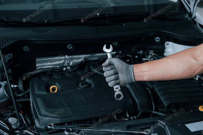 In the shop. Man's hand in glove holds wrench in front of broken automobile