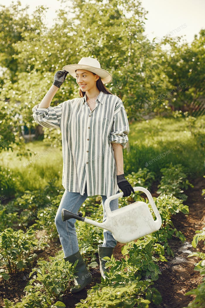 Woman in a hat holding funnel and works in a garden