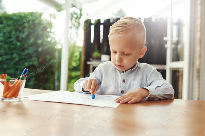 Little boy on an outdoor patio sitting drawing