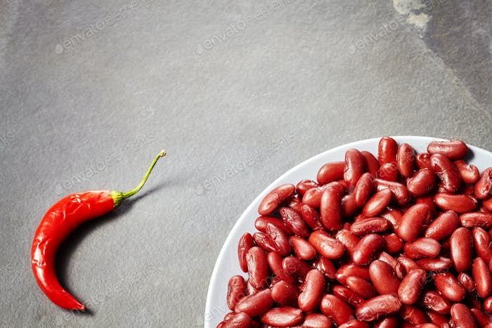 Red kidney bean plate and chili on slate background.