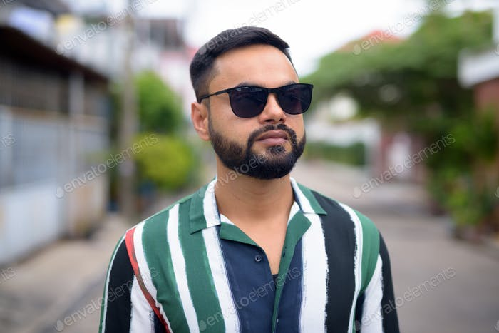 Face of young handsome bearded Indian man with sunglasses thinking outdoors