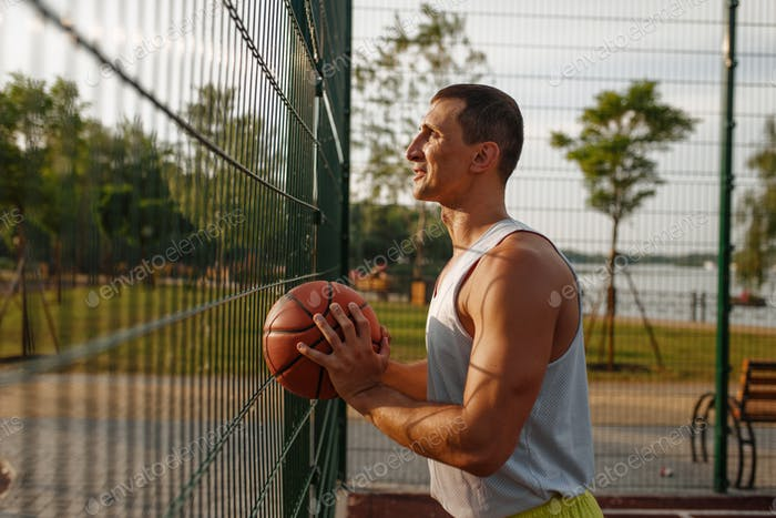 Basketballspieler stehen am Mesh-Zaun
