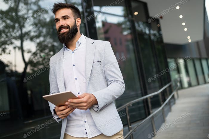 Shot of smiling businessman sitting on bench with digital tablet