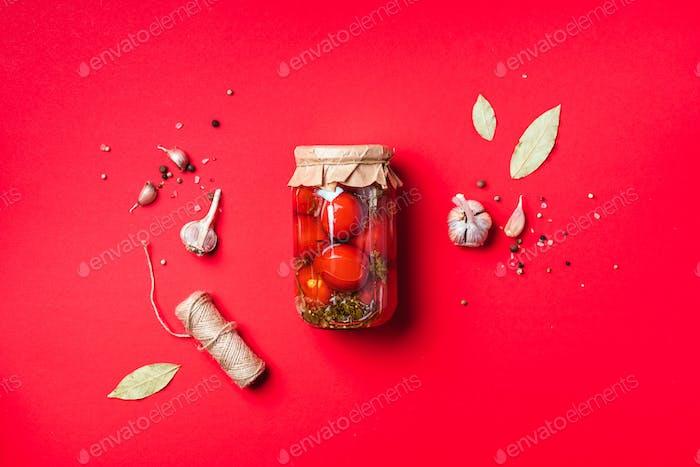 Eingelegte Tomaten in Glas auf blauem Hintergrund. Draufsicht. Flache Lag. Kopierraum. Konserven und konserviert