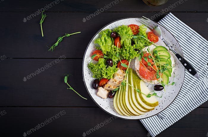 Healthy breakfast. Sandwiches with cream cheese,  salmon, avocado and slice pear on plate.
