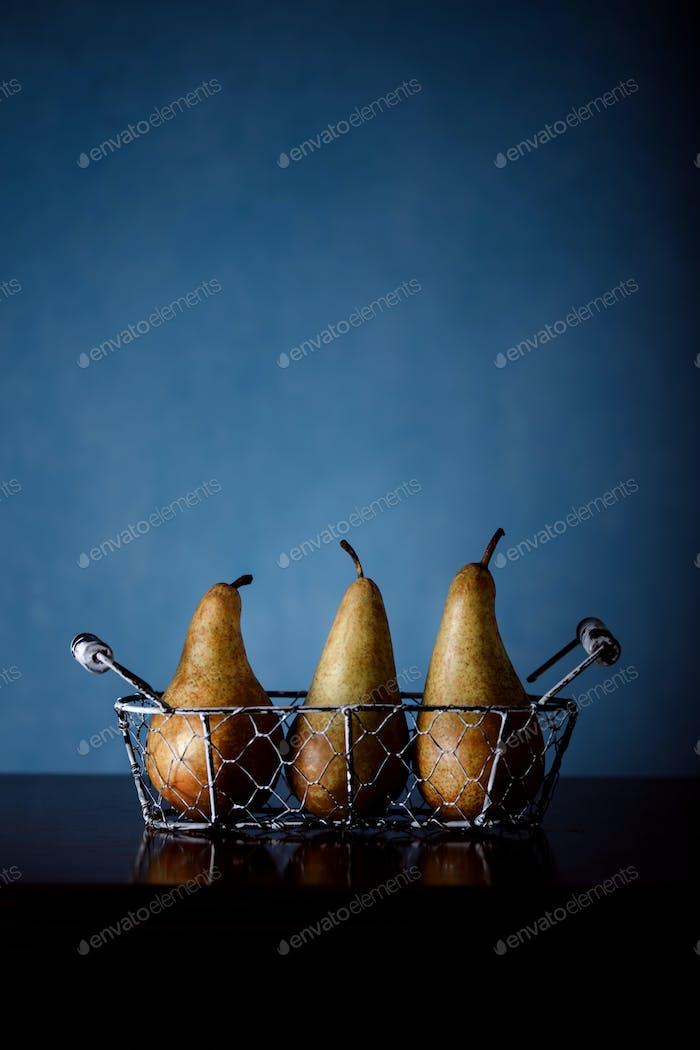 Fine art still life photography of pears on dark blue background.
