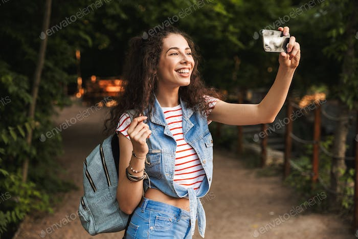Photo of brunette pretty woman 18-20 with backpack, smiling broa