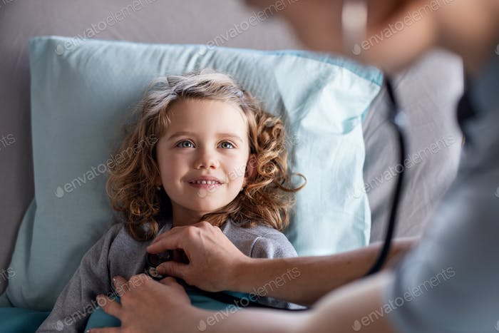 Unrecognizable female doctor examining small girl in bed in hospital.