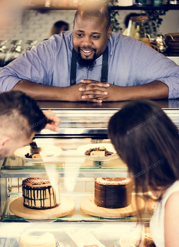 Customers choosing cake at the display fridge