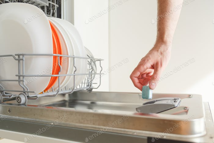 Man puts a chemical dishwasher tablet into the dishwasher machine