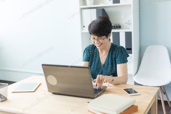 Business people and technology concept - Middle age woman is working at the office with laptop