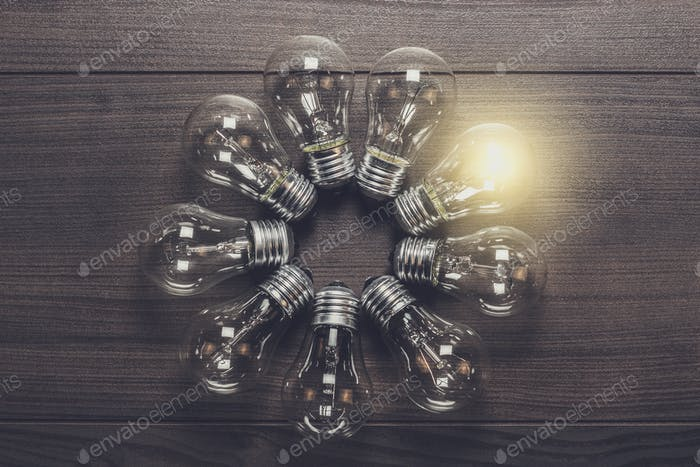 glowing bulb on wooden background uniqueness concept