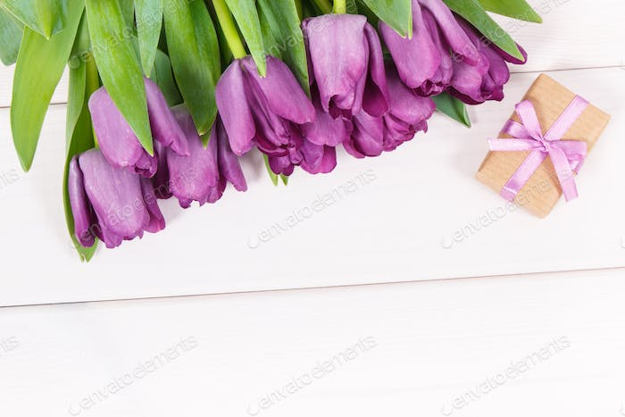 Bouquet of purple tulips and gift for different occasions or celebration on boards