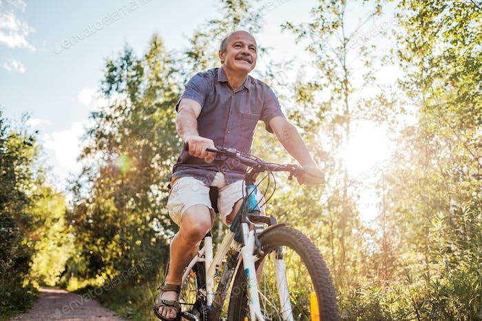 Joyful senior man riding a bike in a park