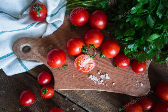 Fresh grape tomatoes with basil and coarse salt for use as cooking ingredients on kitchen board