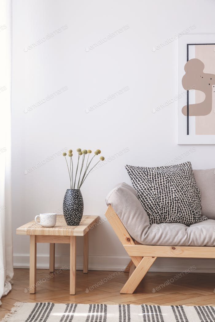 Flowers on wooden table next to beige couch with cushion in flat