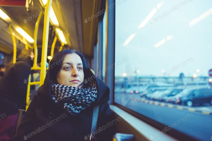 Young handsome caucasian woman sitting on a bus, looking outside