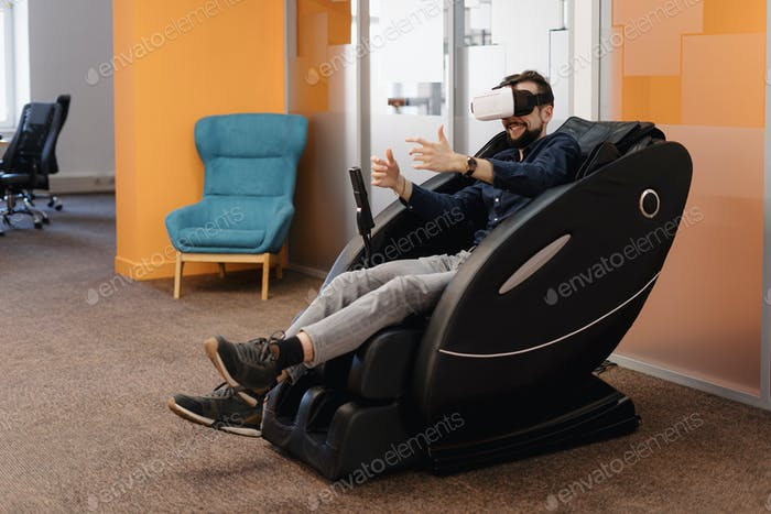 A man in a massaging armchair using VR technology