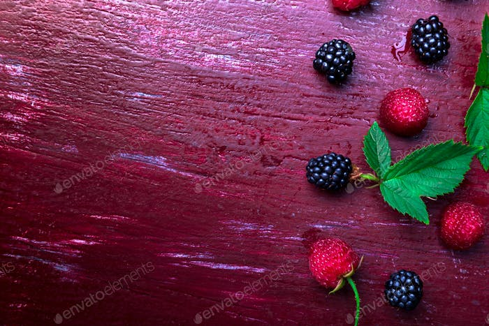 Blackberry and raspberry on red wooden background. Top view. Frame. Flat lay
