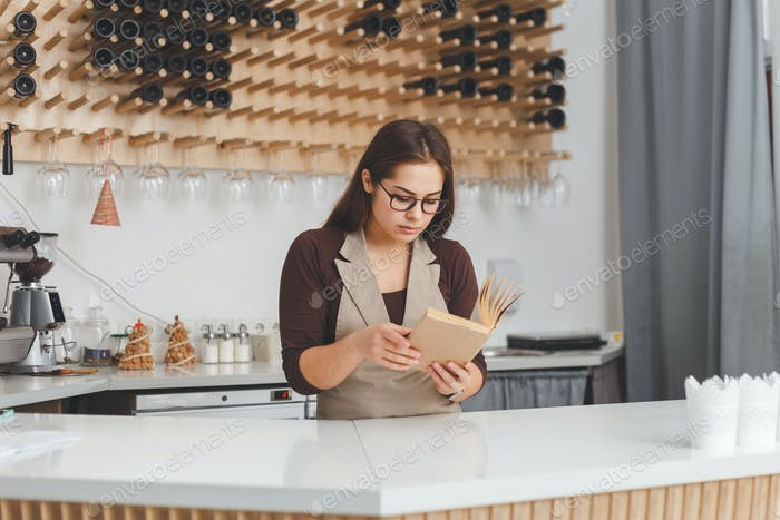 Young housewife standing in the kitchen reading a recipe book