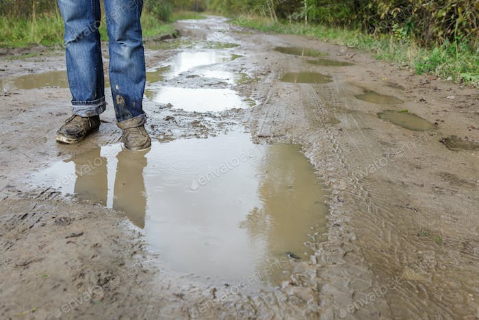 Man in dirty shoes standing in the mud