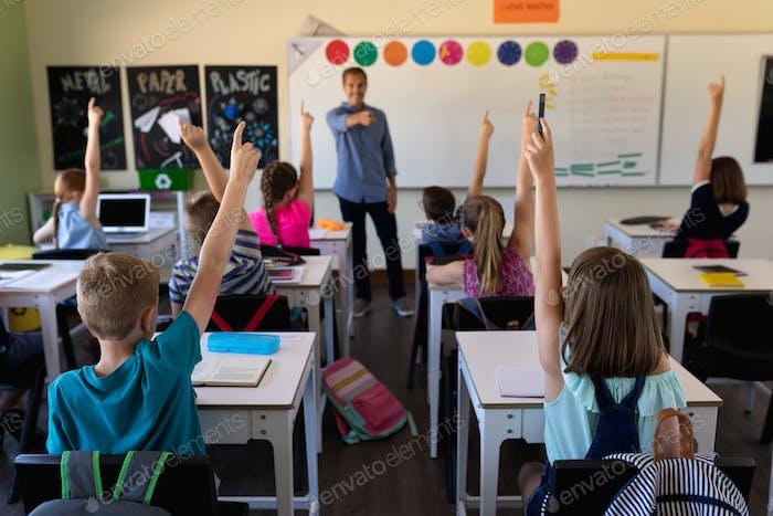 Männlicher Schullehrer, der in einem Grundschulunterricht mit einer Gruppe von Schulkindern steht