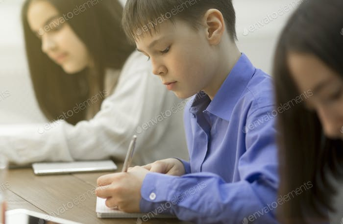 Pupils writing an exam test in classroom