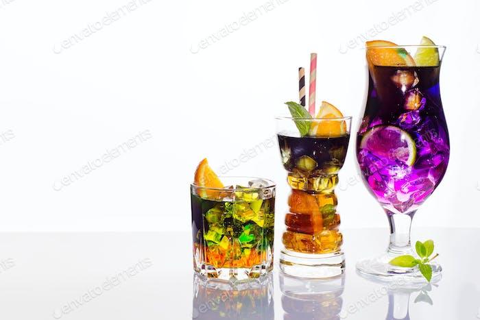 Auswahl an bunten festlichen Getränken, alkoholischen Getränken und Cocktails in eleganten Gläsern auf Weiß