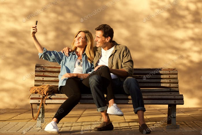 Full length happy couple sitting on park bench taking selfie