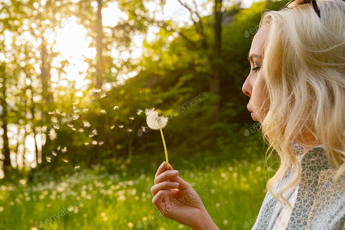 Closeup Of Young Woman Blowing Dandelion Seeds