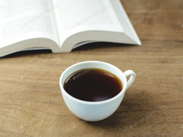black coffee and books on wood background