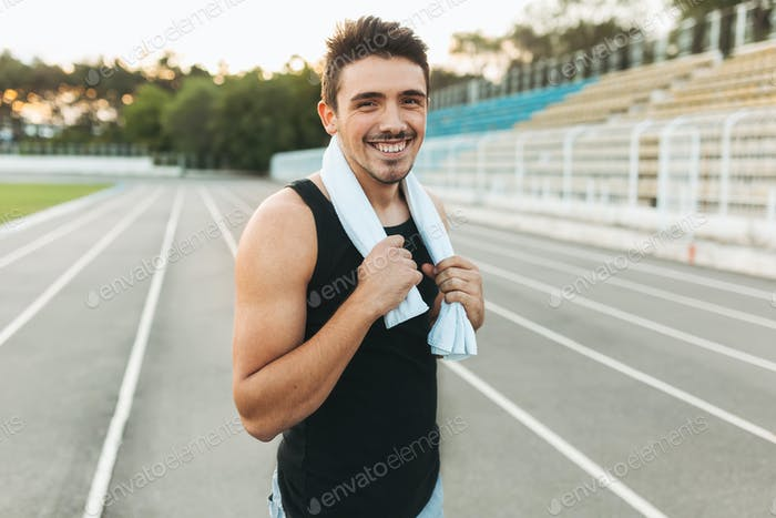 Portrait of a smiling fitness man with towel on shoulders