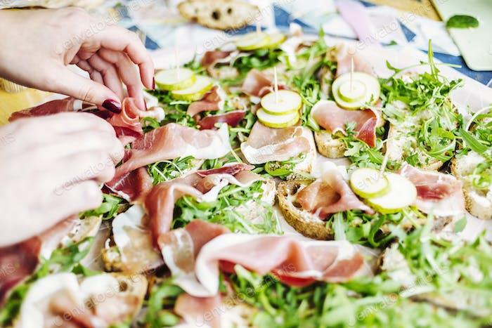 Hände der Frau legen Fleischscheiben auf offene Sandwiches